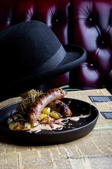 ジャガイモと伝統的なドイツのソーセージを鍋で提供しています。レストランの料理。側面図