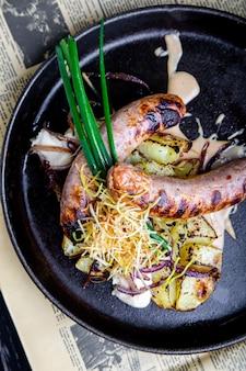 ジャガイモと伝統的なドイツのソーセージを鍋で提供しています。レストランの料理。上面図