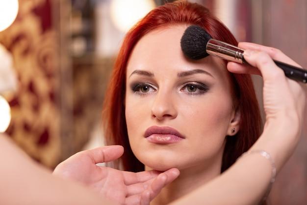 Визажист наносит жидкую тональную основу на лицо женщины