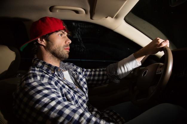 車を運転して深刻な若いハンサムな男の側面図。