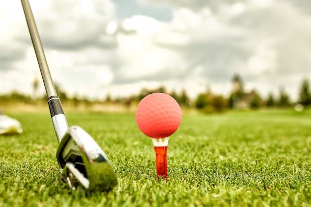 ゴルフ場の穴にあるボール。ゴルフのコンセプト。ヒットする前にゴルフクラブの横にある緑の芝生の上のゴルフボールのクローズアップ。