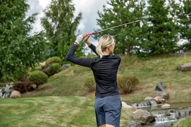 グリーンフィールドでの長いゴルフの試合の後に勝つゴルファーアクション。女の子はゴルフをしています。ゴルフコンセプト、アウトドアスポーツ。