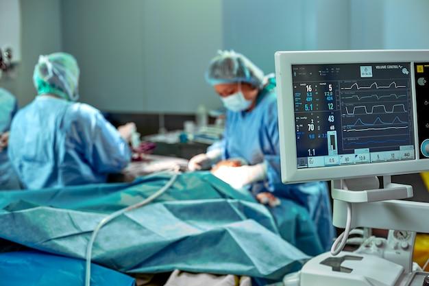 手術室での作業のための外科医のチーム。数人の外科医が実際の手術室で手術を行っています。青い光、白い手袋垂直ショット。
