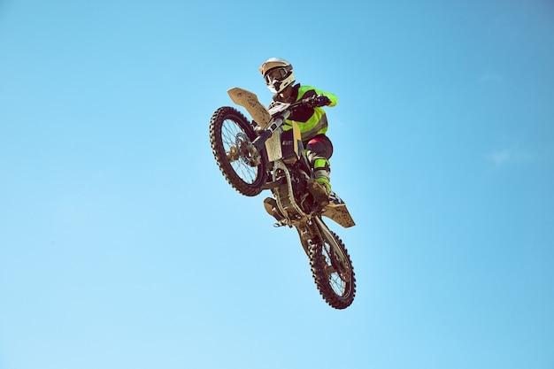 青い空を飛んでいるモーターサイクリスト。極端な概念、オートバイのロングジャンプ。
