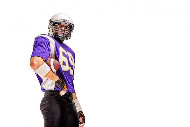 アメリカンフットボール選手の制服姿でポーズを取る