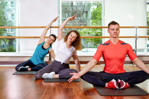 Счастливый многорасовых группа молодых, улыбающихся красивых девушек и стекла в спортивной одежде, делая упражнения йоги в позе лотоса. занятия йогой или фитнес. группа фитнес концепции, групповые тренировки, мотивация.