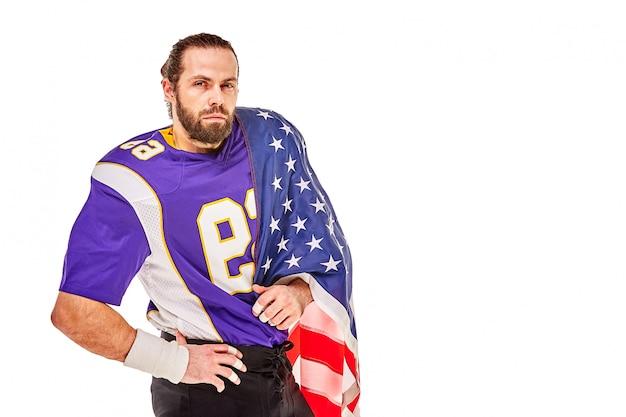 アメリカの国旗と白い背景の上のカメラにポーズをとって愛国心が強いアメリカンフットボール選手。愛国心、行動を促す、アメリカンフットボールのスポーツバナーの概念。