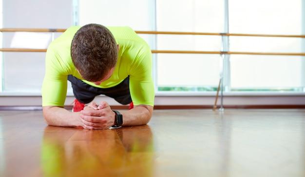 板張りのスポーツウェアを着て自信を持って筋肉質の若い男とロフトのインテリアの床で運動しながら板の位置をやって