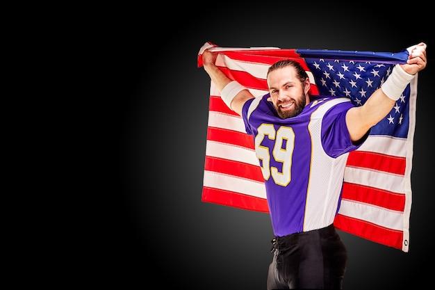 アメリカの国旗と黒の背景にカメラにポーズをとって愛国心が強いアメリカンフットボール選手。愛国心、行動を促す、アメリカンフットボールのスポーツバナーの概念。