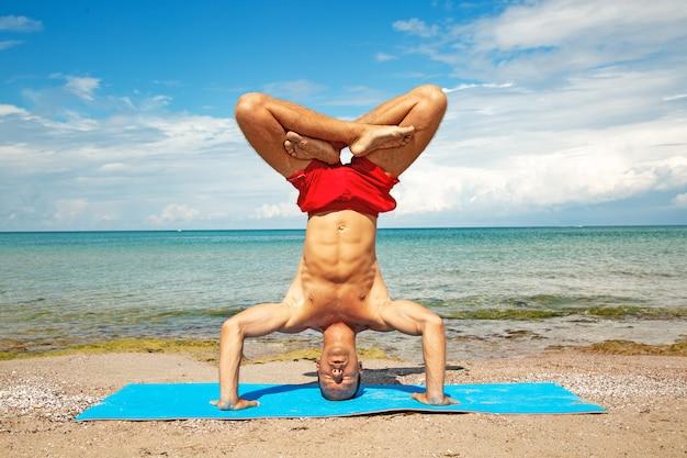フィットネスヨガの練習を行うビーチでアスレチックの男。強度とバランスのためのアクロヨガ要素。