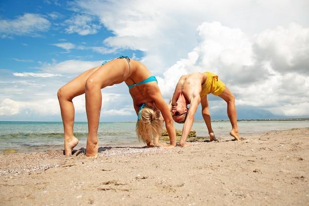 若い男性と女性が一緒にビーチでフィットネスヨガの練習を行います。強度とバランスのためのアクロヨガ要素