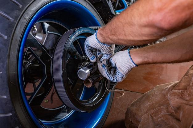 オートバイの修理ガレージで働く男の側ビュー肖像画。手がクローズアップ