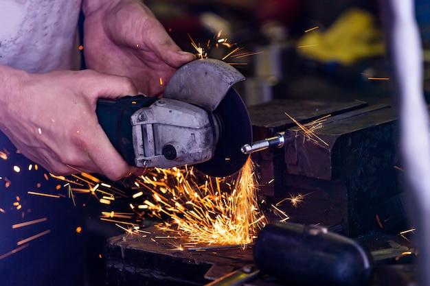 Работник тяжелой промышленности режет сталь с углошлифовальной машиной на автосервисе