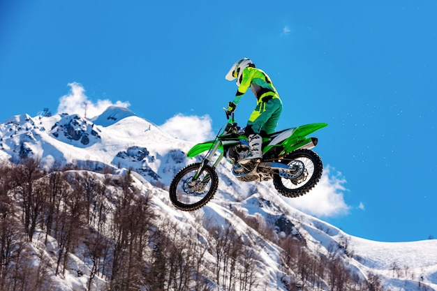 飛行中のオートバイのレーサーは、雪に覆われた山を背景に飛び跳ねて飛び降りる