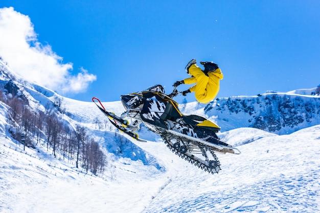 Гонщик на снежной кошке в полете, прыгает и взлетает на трамплине на фоне снежных гор