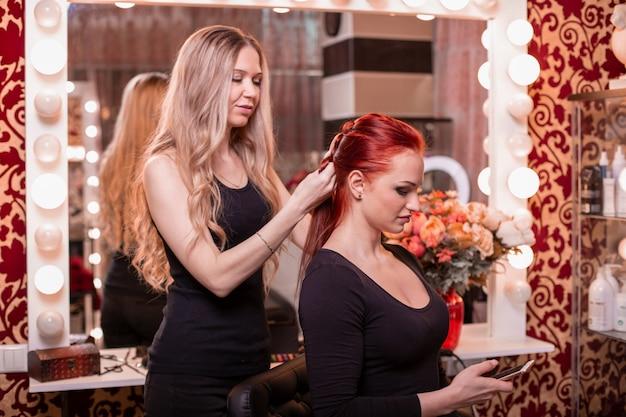 Красивая, рыжеволосая девушка с длинными волосами, парикмахер плетет французскую косу, в салоне красоты.