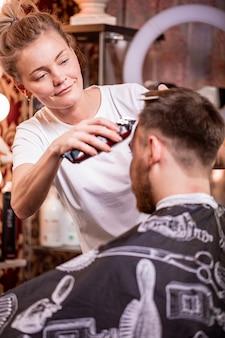 マスターは理髪店で男性の髪とひげをカットし、美容師は若い男性のためにヘアカットを行います。美容コンセプト、セルフケア。