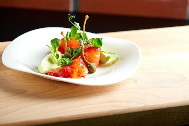 Салат с копченым лососем на деревянном фоне