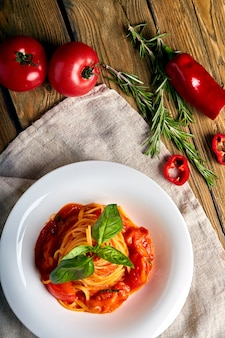 木製の背景にスパゲッティトマトバジル