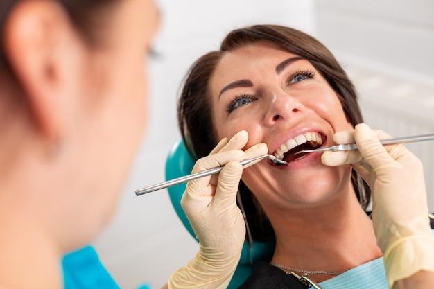 歯科医院で女性の歯に歯列矯正器具を装着する