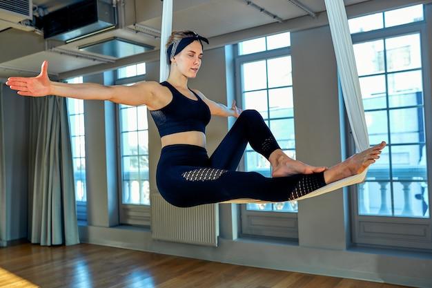 Воздушная йога красивая девушка, тренирующая воздушную йогу, демонстрирует различные упражнения на висячих линиях в комнате для йоги.