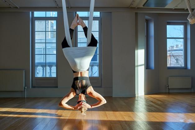 Красивая девушка с аэрофотосъемкой йоги показывает медутирует на свисающие линии с ног на голову в комнате йоги