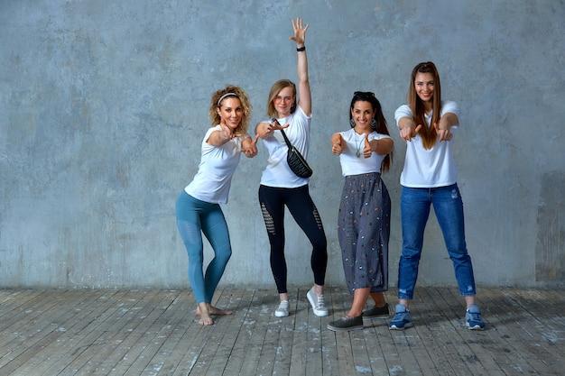 若い女の子のグループは、笑顔で自分の手でジェスチャーを示す壁にポーズを取っています。灰色の背景、スペースを節約。