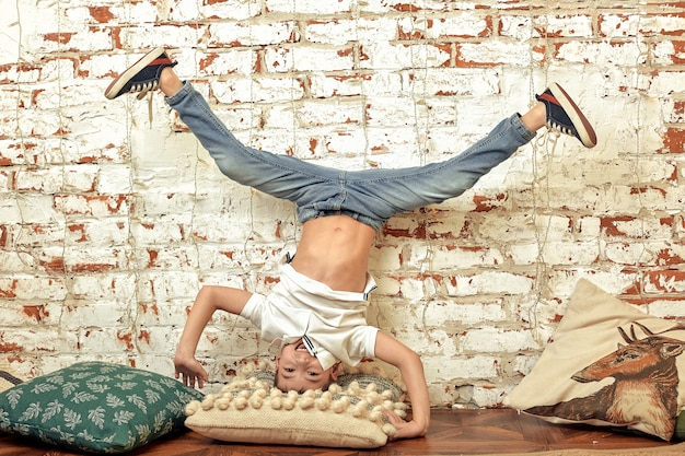 少年はレンガの壁に逆さまに立っています。頭の上に退屈した少年が立っています。レンガの背景、エンターテイメントのコンセプト。
