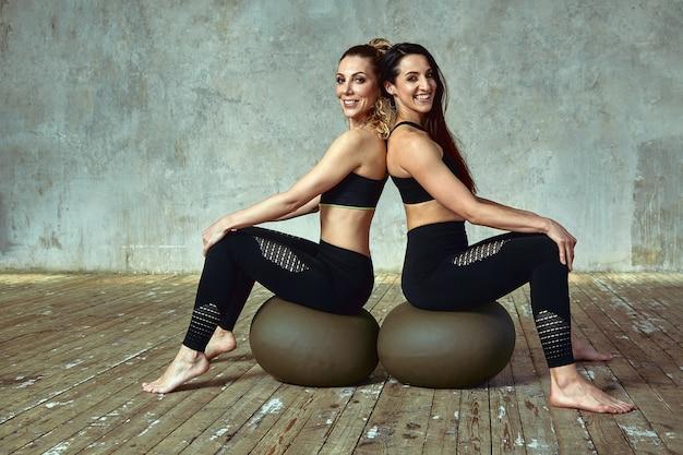 Фитнес-тренировка, две стройные красотки тренируются в тренажерном зале.