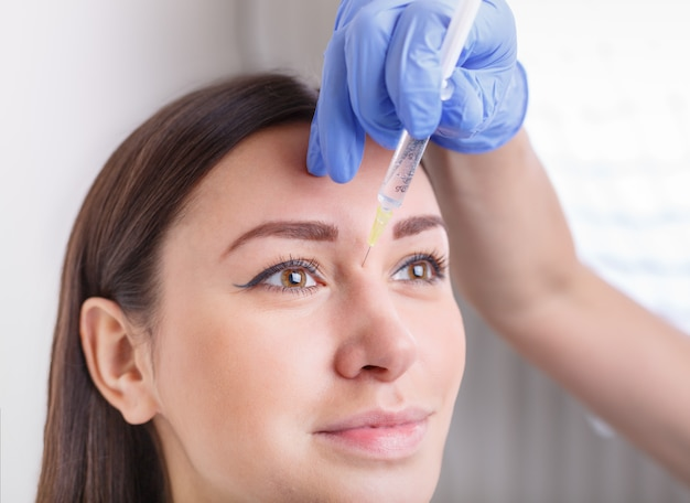 きれいな女性の顔への化粧品の注入