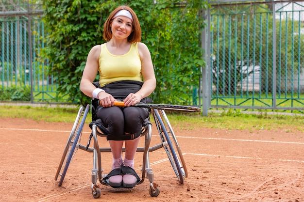 Неработающая молодая женщина на кресло-коляске играя теннис на теннисном корте.