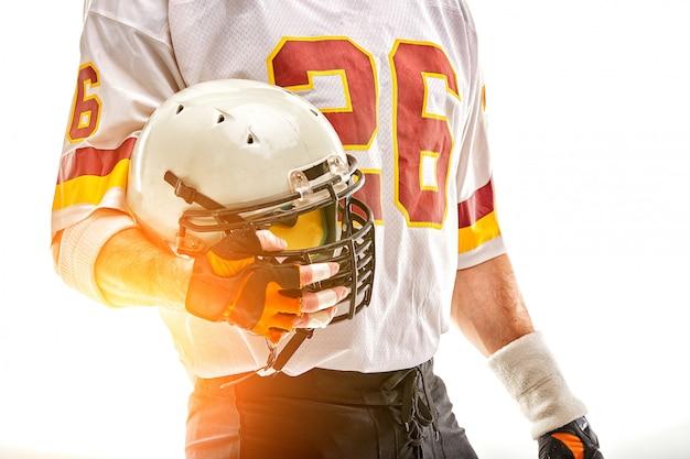 手にヘルメットを持つアメリカンフットボール選手