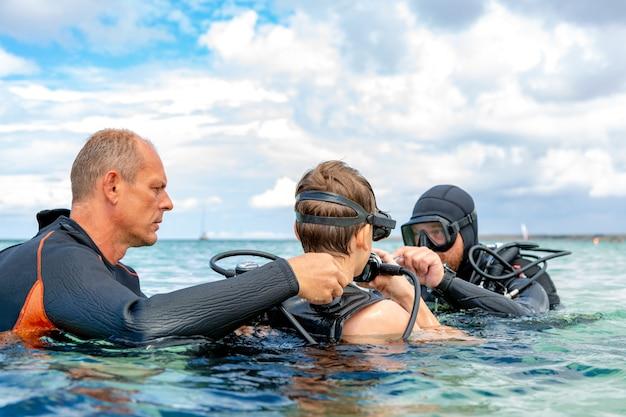 ダイビングのスーツを着た男が少年のダイビングを準備します