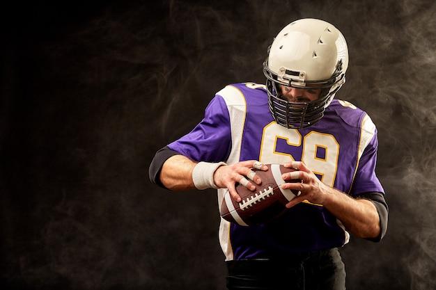 彼の手でボールを保持しているアメリカンフットボール選手