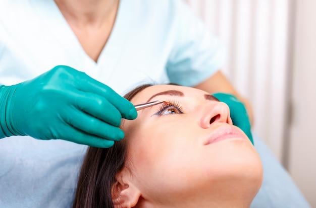 Косметический хирург осматривает клиентку в клинике перед пластической операцией