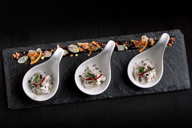Мини-порции сибича из сибаса подаются в красивых китайских ложках на черном плато. концепция питания для общественного питания.