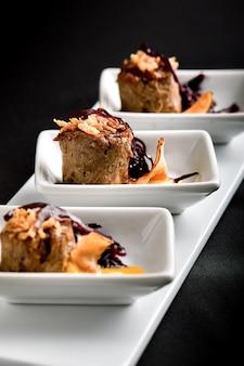 Канапе из говядины с тыквенным соусом, на белых тарелках