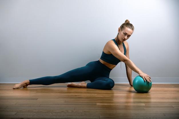 Молодая, красивая, спортивная женщина делает упражнения на фитбол в тренажерном зале. спортивная славянская женщина в синем, зеленом костюме.