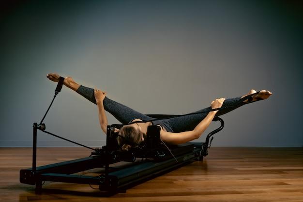 ピラティスを行う若い女性は、リフォーマーベッドで運動します。美しいスリムなフィットネストレーナー