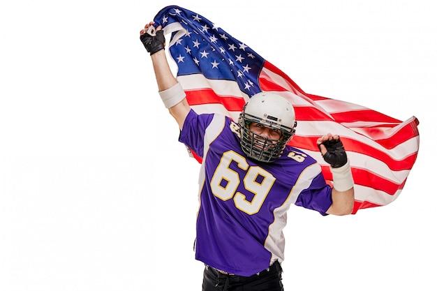 ユニフォームとアメリカ国旗のフットボール選手は勝利を祝います、
