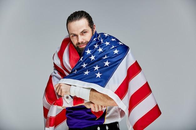 ユニフォームと彼の肩に彼の国を誇りに思うアメリカの旗を持つフットボール選手、