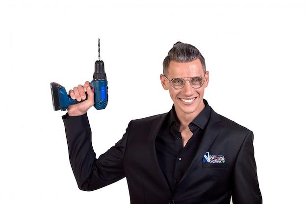 Портрет сумасшедшего смешного молодого человека в черном костюме, улыбаясь с помощью дрели