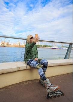 Счастливая женщина в роликовых коньках сидит и делает селфи фото на смартфон на берегу реки