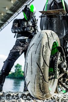 Мотоциклист в шлеме и в защитном костюме стоит под мостом