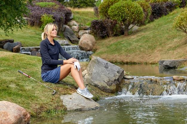 屋外の公園でカメラに笑顔の美しい若い女性。アウトドアレクリエーション、幸せな生活。