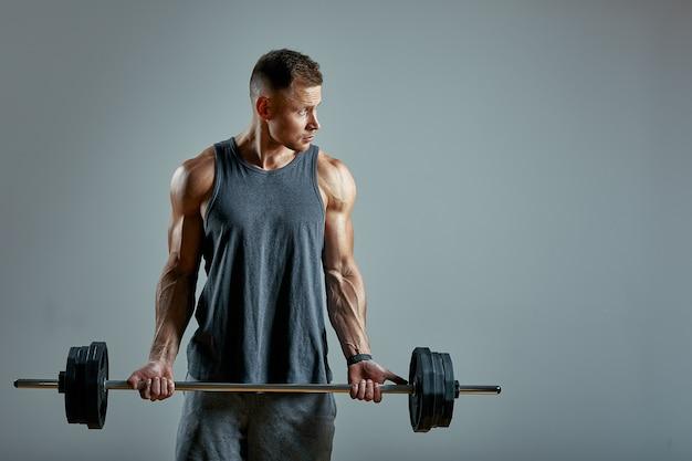バックトレーニング、灰色の背景の上のスタジオでバーベル行をしている男。コピースペース