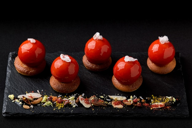 Мини-тарталетки из глазированных сверху ягод красиво разложены на черной тарелке. современный десертный праздничный тарталеточный мусс и красная зеркальная глазурь в форме шапки деда мороза.