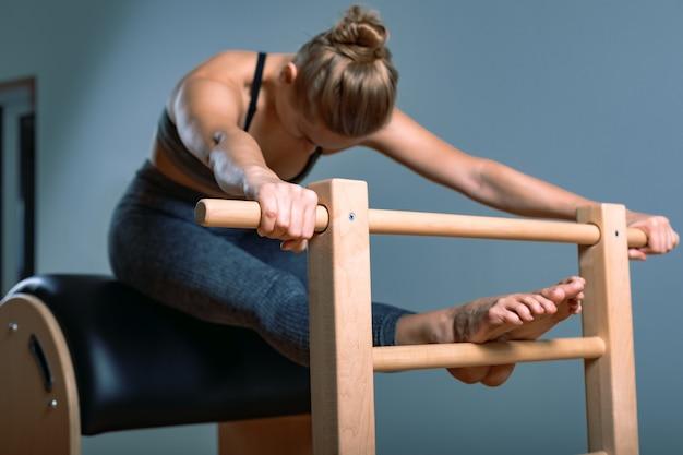 美しい肯定的な金髪の女性は、バレル機器のトレーニング、ピラティス運動を実行する準備されています。フィットネスの概念、特別なフィットネス機器、健康的なライフスタイル、プラスチック。コピースペース、