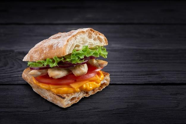 Аппетитный бутерброд на деревянной доске. багет сэндвич с начинкой из салата, ломтики помидора. темный деревянный фон. вид сверху. крупный план. макросъемка.