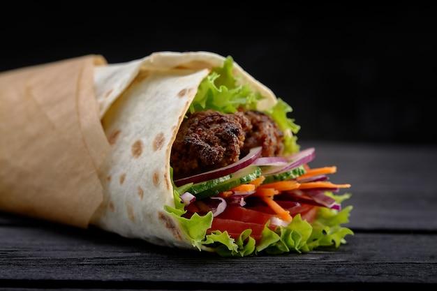 新鮮なサラダトリミングと剃ったロースト肉を添えたおいしいドネルケバブ、茶色の紙にトルティーヤラップでテイクアウトスナックとして提供